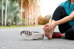 runner massaging her painful foot
